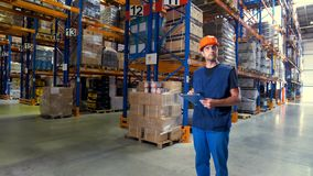 A warehouse employee looks around different aisles. stock video