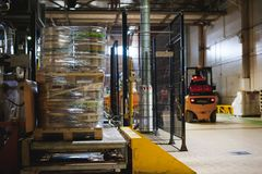 Warehouse employee in Overalls clothes, driver Reachtruck busy working on logistics Moving on loader pallets with beer kegs on lin. E of factory for production Royalty Free Stock Photos