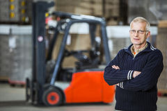 Warehouse employee. A warehouse employee is posing in front of his forklift, he is a proffesional forkliftdriver Stock Images
