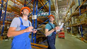 Commercial warehouse workers walk and talk together. stock video