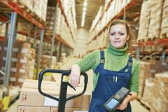 Warehouse female worker at work. Worker in warehouse with bar code scanner stock photo