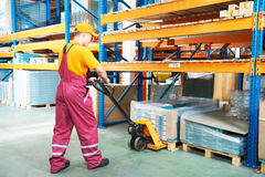 Warehouse female worker at work. Male worker in warehouse working with hand forklift Royalty Free Stock Image