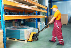 Warehouse female worker at work. Male worker in warehouse working with hand forklift Royalty Free Stock Photo