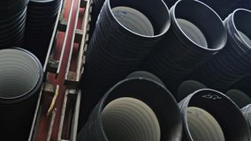 Warehouse of finished plastic pipes industrial outdoors storage site. Manufacture of plastic water pipes factory. Process of making plastic tubes on the stock video footage