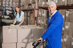 Warehouse foreman smiling at camera with trolley Stock Photography