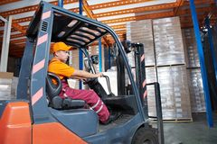 Warehouse forklift loader worker. Warehouse worker distributing goods in a storehouse with forklift truck loader Stock Image
