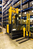 Warehouse forklift in store. Storage logistics in warehouse, store system with modern forklift vehicle and shelves in storehouse Stock Images