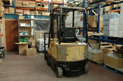 Warehouse and forklift truck. A messy warehouse, with lots of different shape boxes and packets. Also a forklift truck Stock Photos