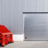 Warehouse garage door. A warehouse garage door and red heavy equipment Royalty Free Stock Photography