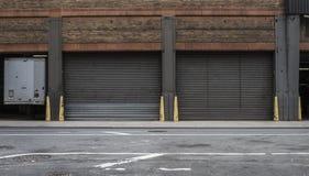 Warehouse garage doors on a city street. Industrial garage doors of a warehouse on a city street royalty free stock photo