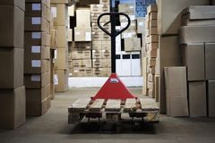 Warehouse with goods in boxes and trolleys for transportation of goods close-up.  Stock Photo