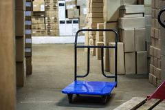 Warehouse with goods in boxes and trolleys for transportation of goods close-up Royalty Free Stock Photos