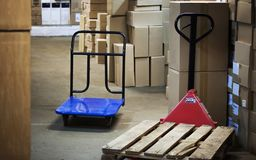 Warehouse with goods in boxes and trolleys for transportation of goods close-up.  Stock Image
