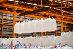 Warehouse handling of starch in jumbo bags. Spread bar lift many jumbo bags at the same time royalty free stock images