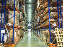 Warehouse or hangar storage racks or shelves with boxes and goods. Industrial logistic delivery and distribution. Toned royalty free stock photo