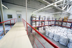 Warehouse with heap of big white sacks on floor and shelves Royalty Free Stock Images