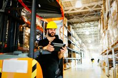 Warehouse worker doing logistics work with forklift loader Stock Photos