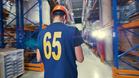 A steadicam shot of a standing warehouse inspector. stock footage