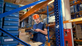 A warehouse inspector studies goods inside opened boxes. stock video footage
