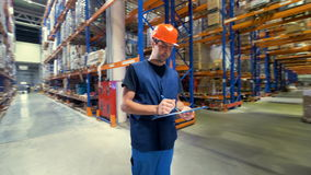 A warehouse inspector taking notes in rotating view. stock video footage