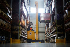 Warehouse Loader Using Forklift Truck. Side view portrait of warehouse worker using reach fork truck to load pallet with boxes on tall rack stock photography