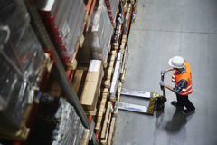 Warehouse Loader at Work. Above view of warehouse loader using forklift cart to pick up pallet with goods Royalty Free Stock Photos