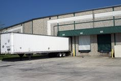 Warehouse loading bays with trailer. Warehouse building loading bays with empty trailer Royalty Free Stock Photos