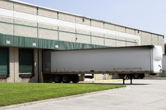 Warehouse loading bays with trailer. Warehouse building loading bays with empty trailer Stock Photo