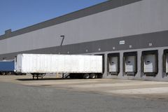 Warehouse loading dock. Trucks unloading and receiving at Warehouse Loading Docks and bays Stock Photography