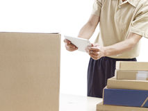 Warehouse man checking packages. Warehouse man working using tablet computer Royalty Free Stock Photos
