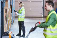 Warehouse Management System. Workers with barcode scanner and stacker. Warehousing. workers using wireless barcode scanner and fork stacker. Warehouse Management Stock Images
