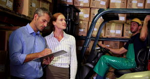 Warehouse management talking with forklift driver behind