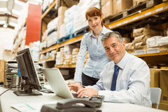 Warehouse management talking and looking at laptop Royalty Free Stock Photos