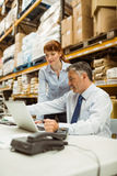 Warehouse management talking and looking at laptop Royalty Free Stock Images