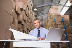 Warehouse manager with blueprint and laptop Royalty Free Stock Images