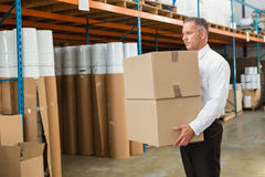 Warehouse manager carrying cardboard boxes Royalty Free Stock Photos
