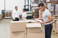 Warehouse manager checking his inventory. In a large warehouse Royalty Free Stock Photography