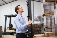 Warehouse manager checking his inventory Royalty Free Stock Photos