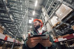 Warehouse manager checking his inventory in a large warehouse. Using the tablet via the Internet is checking stock availability Royalty Free Stock Photos