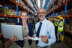 Warehouse manager and client holding digital tablet and clipboard. In warehouse Stock Photo