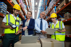 Warehouse manager and client interacting with co-workers. In warehouse Royalty Free Stock Photo