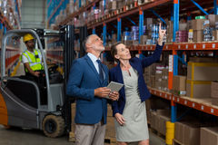 Warehouse manager and client interacting with each other. In warehouse Stock Images
