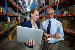 Warehouse manager and client interacting with each other. In warehouse Stock Photo