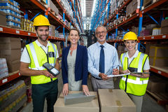 Warehouse manager and client standing with co-workers. In warehouse Stock Photos