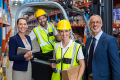 Warehouse manager and client standing with co-workers. In warehouse stock images
