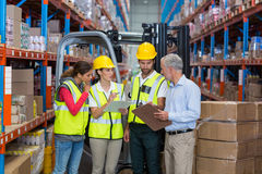 Warehouse manager and co-workers discussing over clipboard Stock Images