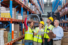 Warehouse manager and co-workers discussing over clipboard Royalty Free Stock Photos