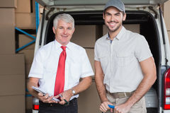 Warehouse manager and delivery driver smiling at camera Stock Photography