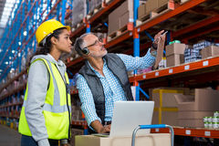 Warehouse manager and female worker interacting while using laptop. In warehouse Royalty Free Stock Photography