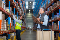 Warehouse manager and female worker interacting while working. In warehouse Royalty Free Stock Photography
